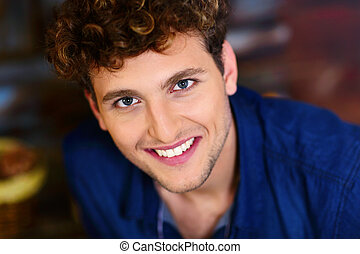 Closeup portrait of a young smiling man with curly hair