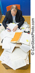 Cluttered Desk - Manager taking notes in a messy office,...