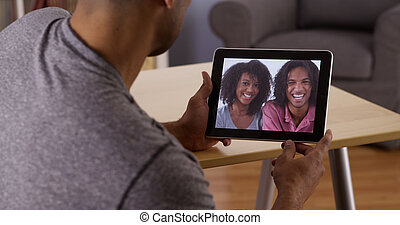 African man talking to relatives with tablet