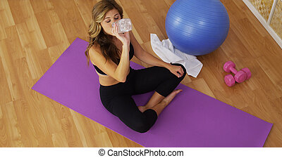 Healthy young woman drinking water after exercising