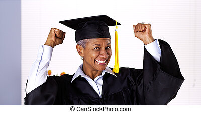 Enthusiastic mature black woman in graduation gown