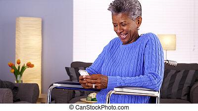 Mature black woman texting on smartphone