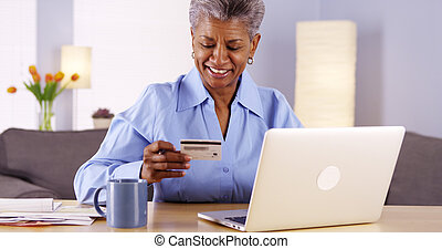 Mature Black woman happily paying her bills