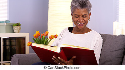 Happy senior black woman looking though photo album
