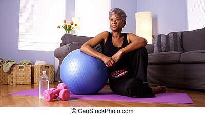 Senior African woman sitting on floor with exercise...
