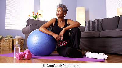Senior Black woman sitting on floor with exercise equipment