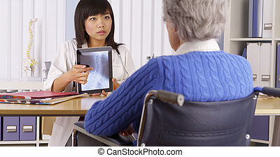 Asian doctor explaining neck x-ray to elderly patient