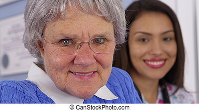 Cheerful elderly patient smiling with Mexican caregiver