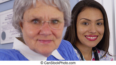 Happy elderly patient smiling with Mexican caregiver
