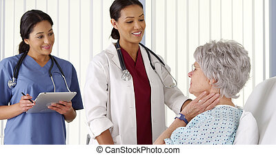 African American doctor talking to elderly woman patient with nurse