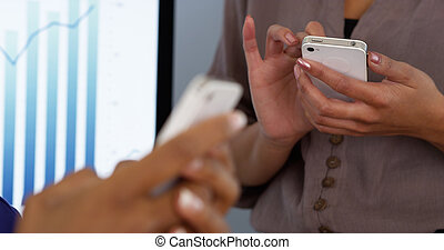 Business women womens hands working on mobile phones