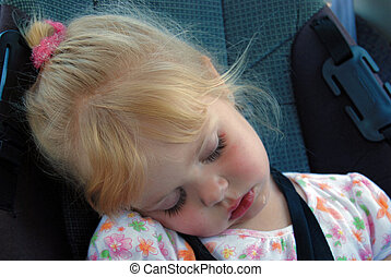 Backseat Nap - Little girl napping in a car seat.