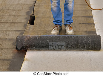 Worker preparing part of bitumen roofing felt roll for...