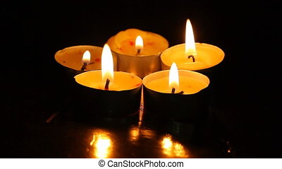 Five small burning candles agains