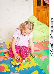Happy little girl playing with blocks in the room