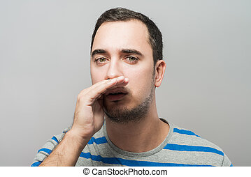 Man holding hands near the mouth