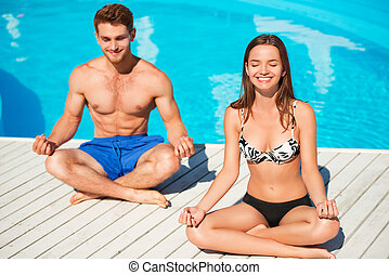 Young couple practicing yoga near swimming pool - Happy...
