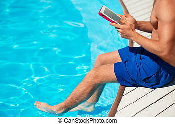 Close-up of man using tablet computer near by swimming pool...
