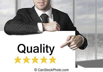 businessman pointing on sign quality - businessman in black...