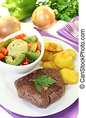 Ostrich steak with crispy baked potatoes on bright...
