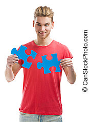 Young man holding a puzzle piece - Good looking young man...