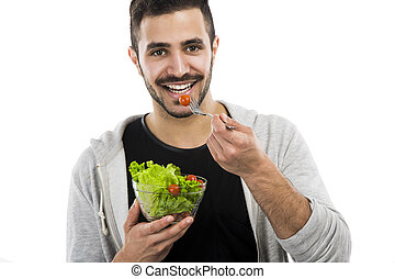 Young man eating a salad - Happy young man eating a salad,...