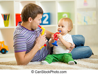 Happy family dad and son play musical toys