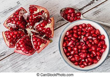 Juicy Pomegranates - Pomegranate seeds in a plate and half...