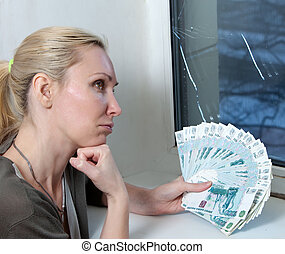 The housewife upset and counts money for repair of a window which has burst in a frost