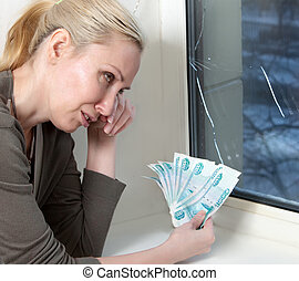The housewife cries and counts money for repair of a window which has burst in a frost