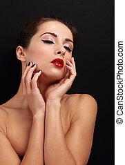 Beautiful enjoying makeup woman touching her health face...
