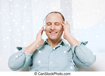 smiling man in headphones listening to music - technology,...