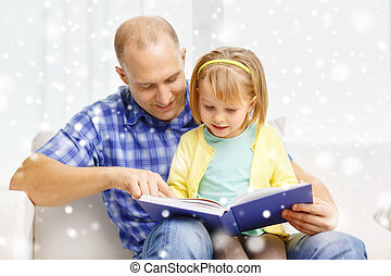 smiling father and daughter with book at home - family,...
