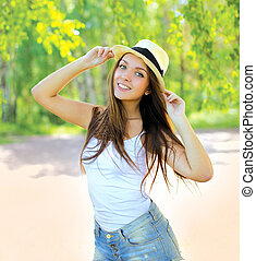 Pretty young girl in summer hat having fun outdoors in warm...