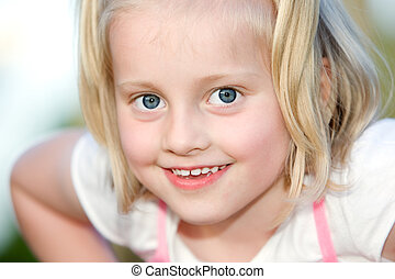Young child looks happy into the camera