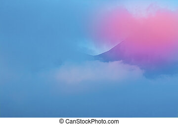 Blue and pink clouds cover the mountain sunset landscape