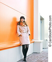 Fashion pretty woman in coat and hat posing against colorful...