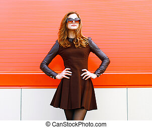 Pretty woman in black dress and sunglasses posing outdoors...