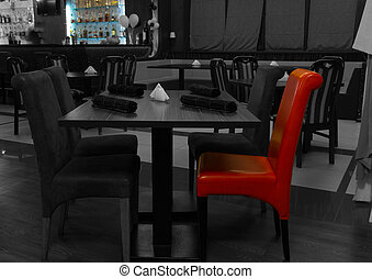 Greyscale restaurant interior with a red chair