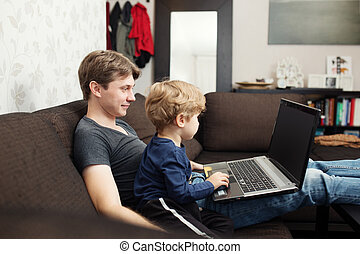 Father and son using laptop on sofa in house
