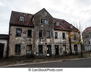 Abandoned house with devasted facade and broken windows
