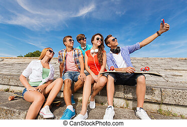 group of smiling friends with smartphone outdoors -...