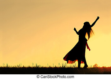 Woman Dancing Silhouette - A woman wearing a long skirt,...