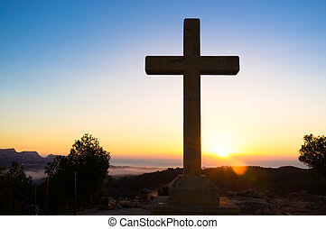 Cross - Huge stone cross against the background of a sunrise