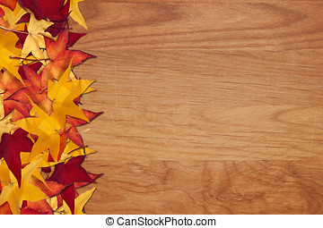 Fall leaves on wood grain background - Colorful autumn...
