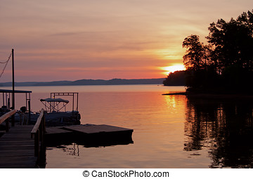 Boat dock at dawn - The sun rises over a calm lake near...