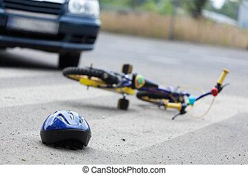 Children bike on the road - A small bike and a helmet lying...