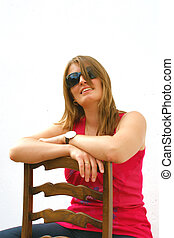 Confident - young confident woman wearing sunglasses sitting...