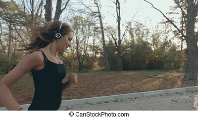 Beautiful girl listening to music on headphones and runs through the park