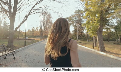 Athletic girl runs through the empty park, view from the...